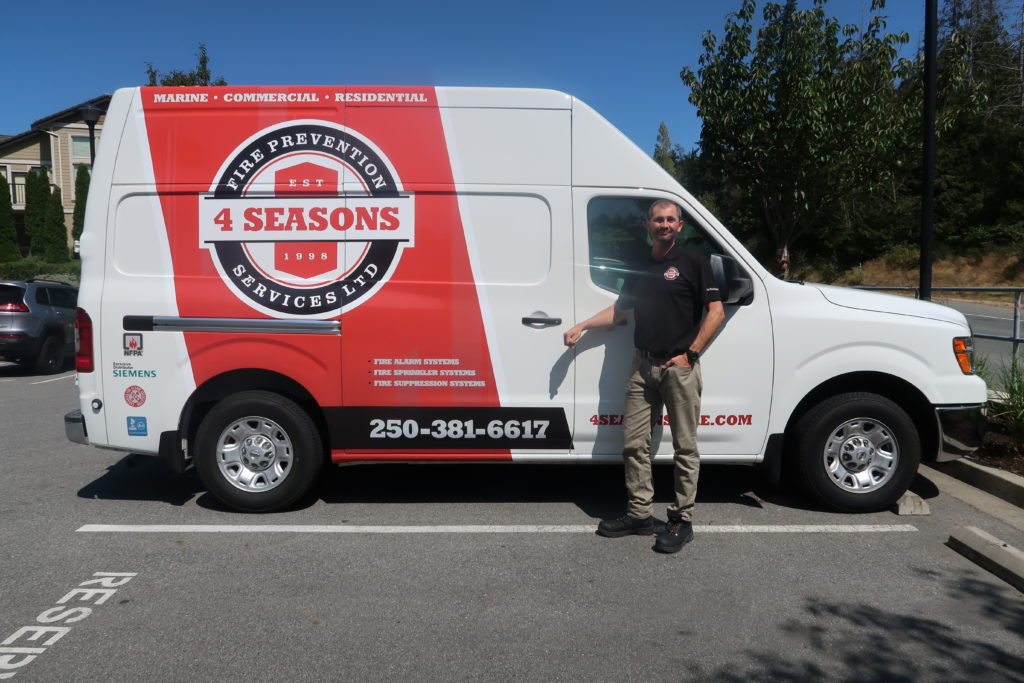 owner standing beside the 4 seasons fire company car